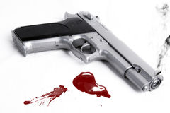 Smoking gun and blood splatter. On the white ground stock image