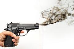 Smoking gun. Hand holding a smoking gun over white royalty free stock photo