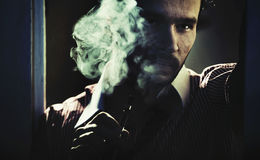 Smoking handsome man with serious look Stock Image