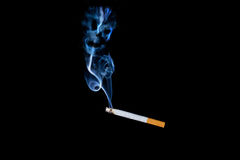 Smoking is harmful to your health. Smokes a cigarette on a black background, is harmful to health Stock Photography