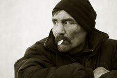 Homeless man smoking a cigarette Stock Images