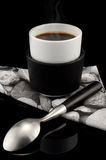 Smoking hot cup of expresso over black background. Smoking hot cup of espresso with fancy napkin, silver spoon over black background stock image