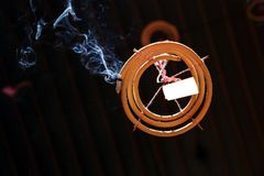 Spiral shaped Chinese prayer joss stick. Smoking incense Spiral shaped Chinese prayer joss stick hanging from the ceiling Royalty Free Stock Image