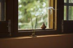 Smoking incense sticks on the window stock photo