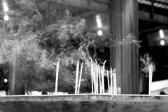 Smoking incense in the temple. (Black and white scene Royalty Free Stock Photos