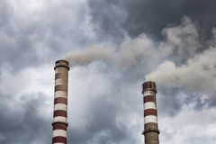 Smoking industrial chimneys in dark clouds. Concept for environmental protection Stock Photo