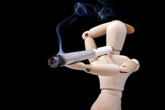 Smoking a joint. Wooden mannequin, relaxing, smoking a joint, isolated on black background Royalty Free Stock Photo