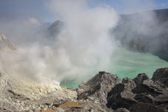 Smoking Kawa Ijen. Colorful crater lake at the Kawa Ijen in Java, Indonesia Stock Photo