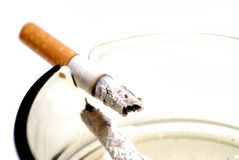 Smoking kills. Picture of half burned cigarette in ash tray Stock Photo