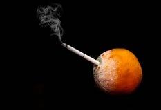 Smoking kills image of rotten orange on a black background.  Royalty Free Stock Photos