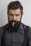 Smoking man with beard Royalty Free Stock Images