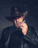 Smoking man with a beard and mustache wearing a cowboy hat. Hipster colors Royalty Free Stock Photo