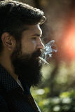 Smoking man in forest Stock Photo