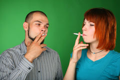 Smoking man and woman on green background Royalty Free Stock Images
