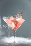 Smoking martini cocktail. In a conical glass with wafting vapour and splashing droplets from a falling cherry for a dramatic effect over a grey background Royalty Free Stock Images