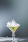 Smoking martini cocktail. In a conical glass with wafting vapour and splashing droplets from a falling olive for a dramatic effect over a grey background Stock Photography