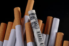Smoking Money. A cigarette wrapped in a dollar bill on a pile of other cigarettes Stock Image