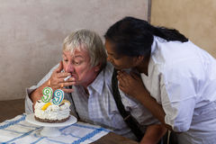 Smoking old man on birthday Stock Photography