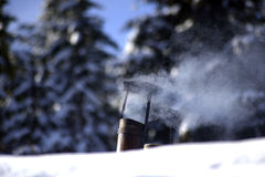 Smoking old tin  chimney on a snowy roof Stock Image