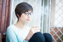 Smoking outdoor, young woman tobacco addicted. Young pretty woman smoking and relaxing outdoor Stock Image