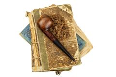 Smoking pipe and antique books. Tobacco pipe on ancient books. Relax by reading old books. Smoking. Stock Images