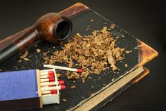 Smoking pipe and antique books. Tobacco pipe on ancient books. Relax by reading old books. Smoking. Royalty Free Stock Photos