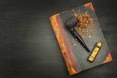 Smoking pipe and antique books. Tobacco pipe on ancient books. Relax by reading old books. Smoking. Royalty Free Stock Image