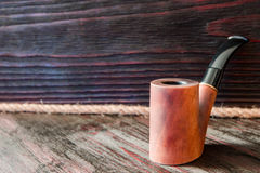 Smoking pipe on a background of mahogany.  Royalty Free Stock Photos