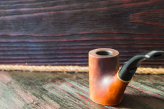 Smoking pipe on a background of mahogany.  Royalty Free Stock Photo