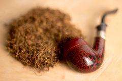 Smoking pipe with tobacco leaves  Stock Photography