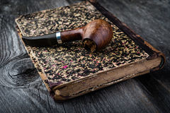 Smoking pipe and tobacco on old book Stock Photography