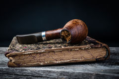 Smoking pipe and tobacco on vintage book Royalty Free Stock Photography