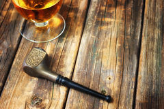 Smoking pipe and whiskey glass on wooden table Stock Photography