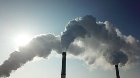 Smoking pipe. White smoke poured from chimney the background of a clear blue sky. Thick white smoke swirled and poured from the chimney with a large stream stock video footage
