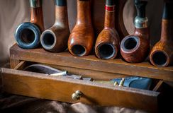 Smoking pipes on display with accessories. Display of smoking pipes on a wood rack, with an accesory drawer of pipe tools stock image