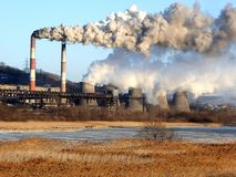 Smoking chimneys and evaporating cooler towers of electric power station over the frozen winter river stock images