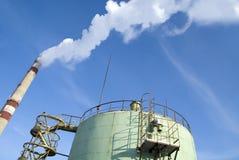 Smoking pipes near tank on blue sky. Smoking pipe near tank on blue sky Royalty Free Stock Images