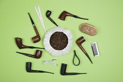 Smoking pipes and pipe smoking accessories. Top view. Different smoking tobacco pipes and pipe smoking accessories on green background. Top view Stock Image