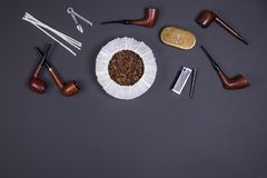 Smoking pipes and tobacco accessories on dark background. Top view. Different smoking tobacco pipes, tobacco in the can and tobacco accessories on dark Royalty Free Stock Photo