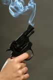 Smoking Pistol. Photo of a smiking pistol on a grey background Royalty Free Stock Photography