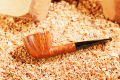 Smoking polished pipe and wood chips Royalty Free Stock Photos