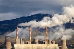Smoking power station chimneys. View of smoking chimneys of power station polluting atmosphere stock photo