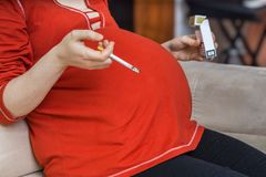 Smoking in pregnancy. Bad pregnant mother holds cigarette in hand Royalty Free Stock Photos
