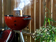 Smoking Red Grill with Flowers. And fence outdoors in the back yard Royalty Free Stock Photos