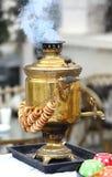 Ukraine, Kiev. Samovar. A smoking Russian samovar with bagels. Ancient samovar on the coals stock photos