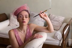 Smoking 1920s woman. Sensual 1920s woman in pink flapper dress sitting on an antique chaisee longue or recliner royalty free stock image