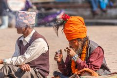 Smoking Sadhu with orange turban at Bhaktapur`s Durbar Square