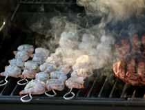 Smoking Shrimp on the Grill. Skewered shrimp cooking (and smoking) on a barbecue grill along side beef Royalty Free Stock Image