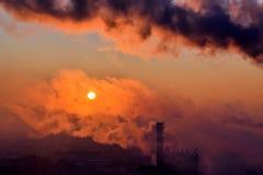 Smoking smoke stack at sunrise Royalty Free Stock Photo