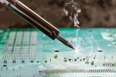Smoking soldering iron Stock Photos